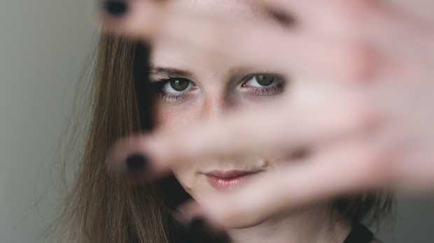 Kobieta zasłania sobie twarz dłonią
