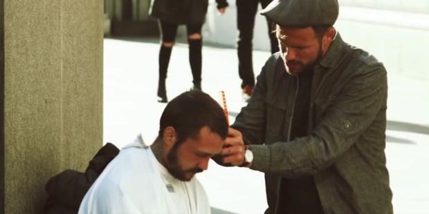 Mężczyzna obcina włosy bezdomnemu na ulicy