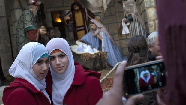 Dwie muzułmanki fotografują się na tle chrześcijańskiej szopki przed Kościołem Narodzenia w Betlejem, fot. AP PHOTO/BERNAT ARMANGUE