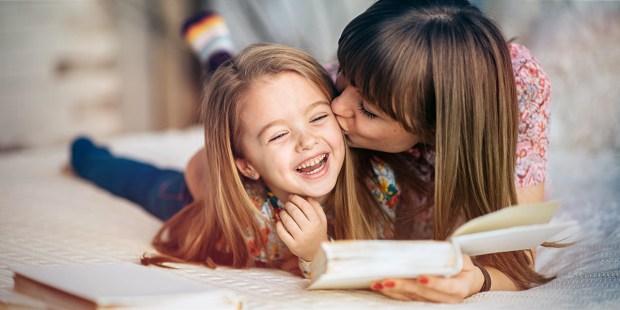 Matka całuje córkę w policzek