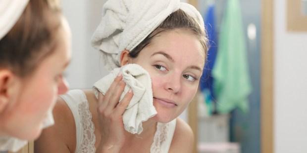 Kobieta myje twarz przed lustrem