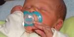 Małe dziecko ze smoczkiem w ustach