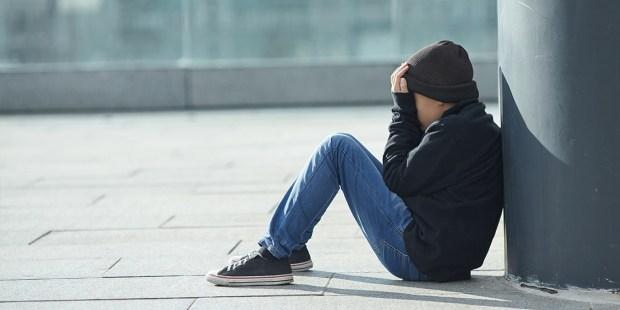 Smutny chłopiec siedzi na ulicy