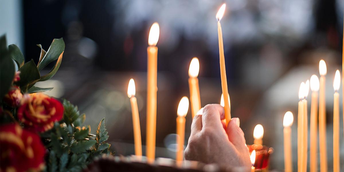 Ręka zapalająca świeczki w cerkwii