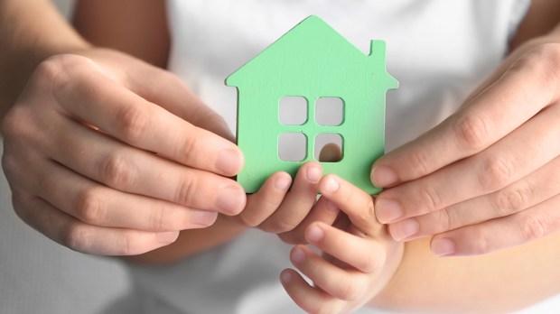 Dziecko i rodzic trzymają w rękach dom