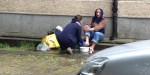 Kobieta myje nogi bezdomnemu na ulicy