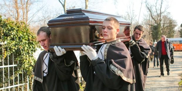 Grabarze niosą trumnę na cmentarzu