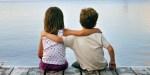 Chłopiec i dziewczynka siedzą nad jeziorem