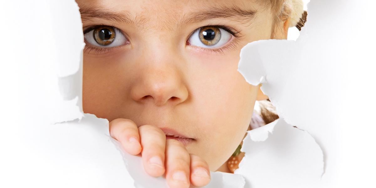 Przestraszone dziecko patrzy przez dziurę