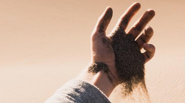 Ręka i przesypujący się piasek