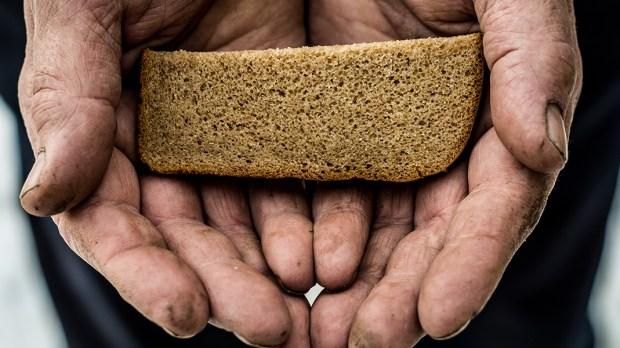Biedny człowiek trzyma w dłoniach kawałek chleba