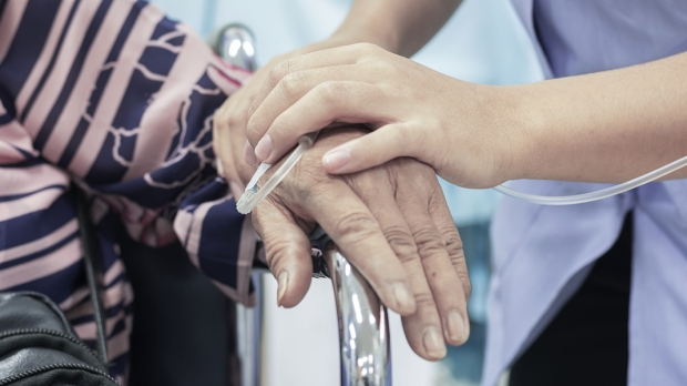 Opiekun trzyma chorą osobę za rękę