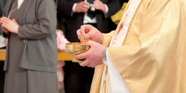 Ksiądz trzymający Komunię Świętą w dłoniach