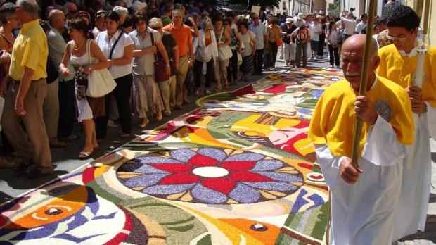 Procesja idąca ulicami ubranymi w kwiaty