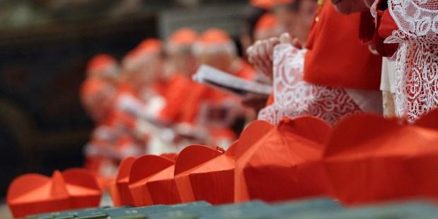 Birety kardynalskie leżą na stole