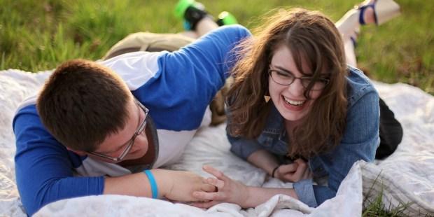 Para leży na kocu na trawie