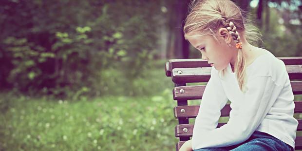Smutna dziewczynka na ławce