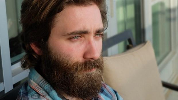 Mężczyzna z brodą patrzy w świat
