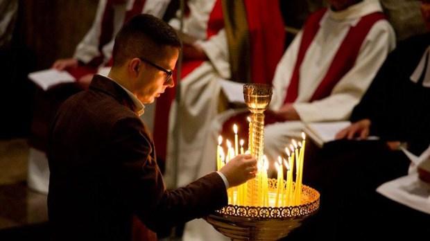 Mężczyzna zapala świeczkę w czasie liturgii