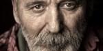 Mężczyzna z brodą patrzy na wprost obiektywu