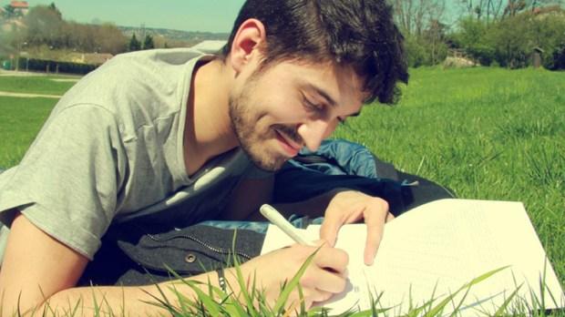 Mężczyzna leży na trawie i notuje w zeszycie