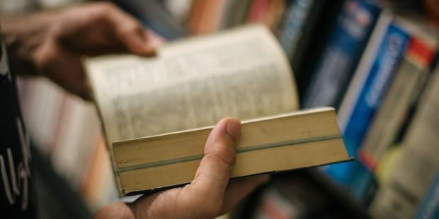 Mężczyzna trzyma w dłoniach starą książkę