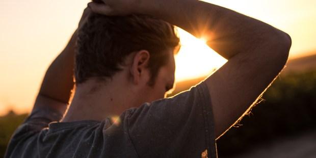 Mężczyzna patrzy się na zachodzące słońce