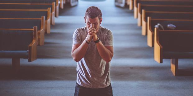 Mężczyzna modli się na środku kościoła