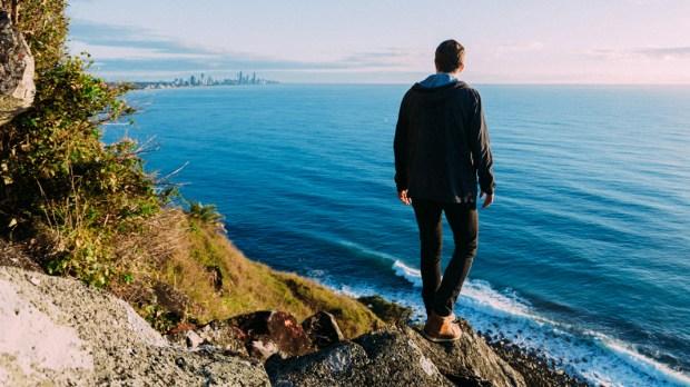 Mężczyzna stoi nad brzegiem morza