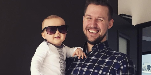 Marcin Gomułka z synem na rękach