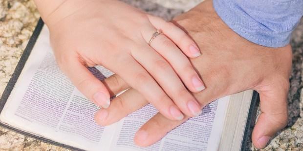 Ręce położone razem na Biblii