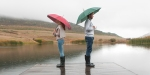 Para z parasolkami stoi nad jeziorem