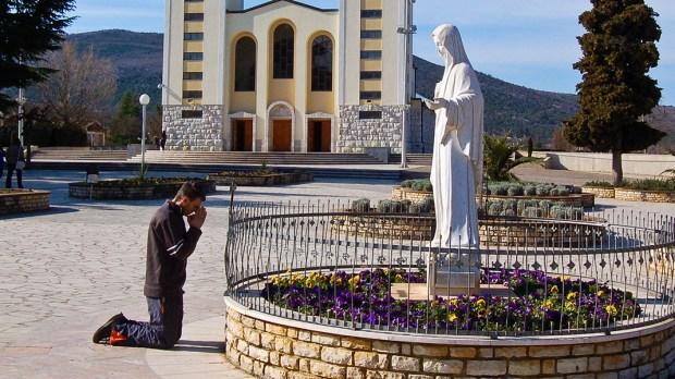 Mężczyzna modli się przed figurą Maryi