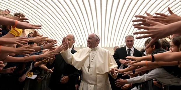 Wyciągnięte ręce młodych ludzi,. którzy chcą przywitać się z papieżem