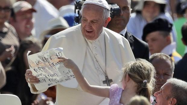 Papież Franciszek z dziewczynką pokazującą swój rysunek