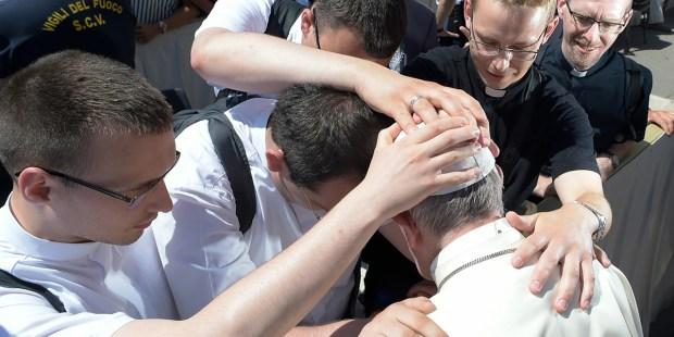 Neoprezbiterzy modlą się nad papieżem Franciszkiem