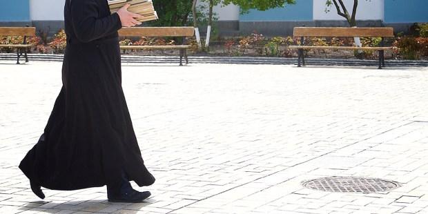 Ksiądz idący po ulicy w sutannie