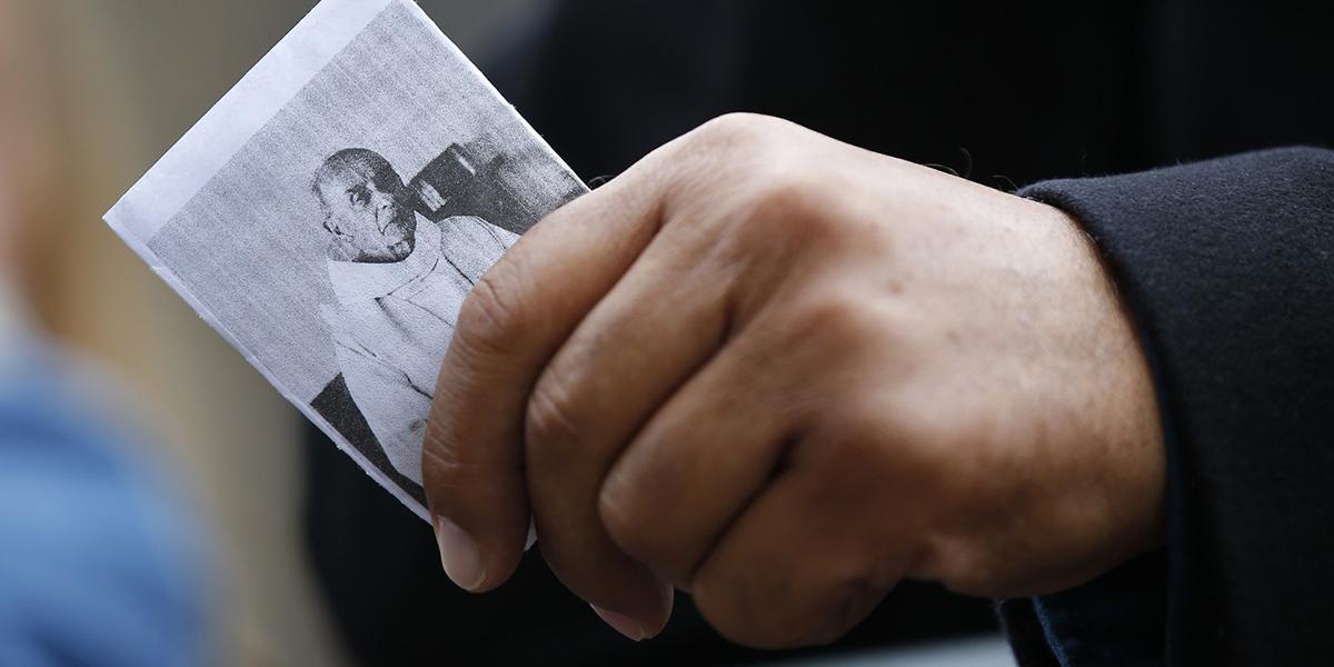 Mężczyzna trzyma obrazek z ks. Hamelem