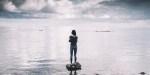 Kobieta stoi na kamieniu w środku morza