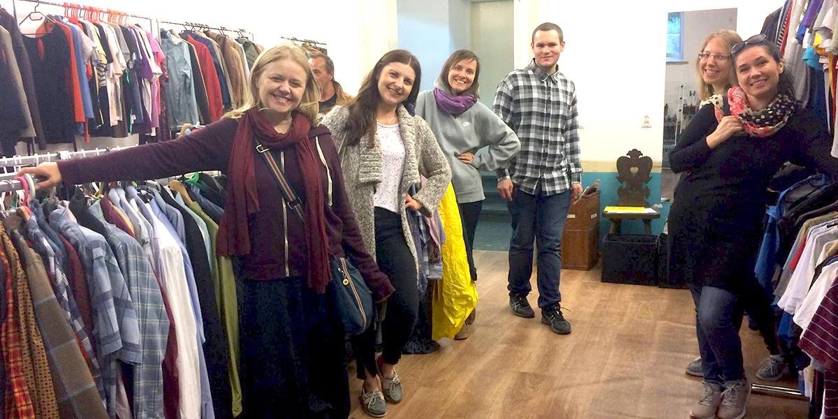 Członkowie wspólnoty stoją przy wieszakach pełnych ubrań