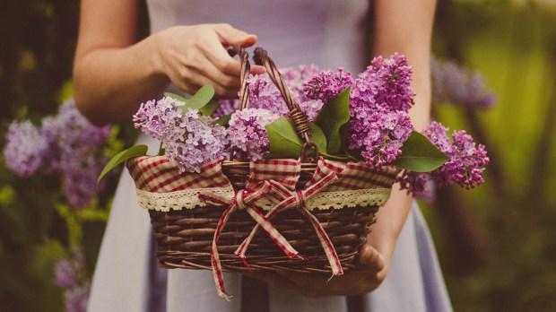 Kobieta trzyma w rękach koszyk pełen kwiatów