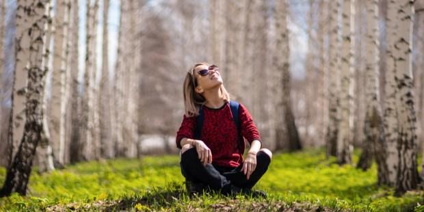 Dziewczyna siedzi na trawie w lesie