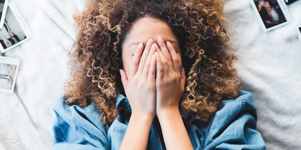 Dziewczyna zakrywa twarz dłońmi