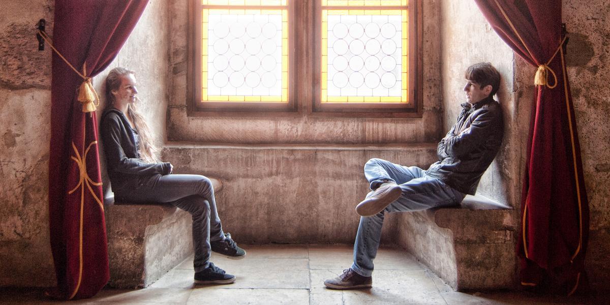 Chłopak i dziewczyna siedzą przy oknie