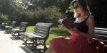 Kobieta na ławce w parku czyta książkę