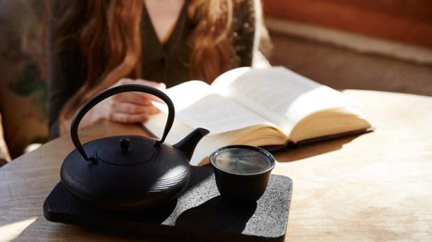 Kobieta czyta książkę przy czajniku z herbatą