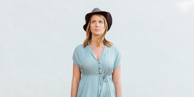 Kobieta w niebieskiej sukience i kapeluszu