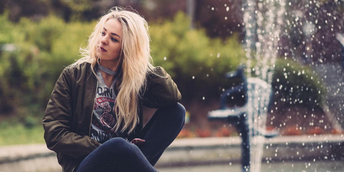 Dziewczyna siedząca na brzegu fontanny