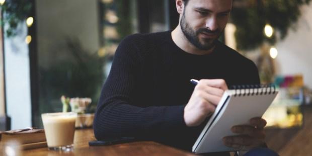 Mężczyzna zapisuje coś w notatniku w kawiarni