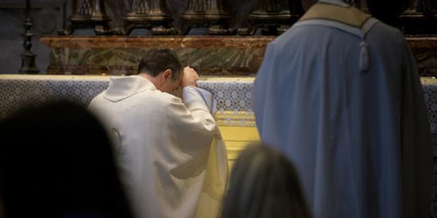 Ksiądz modli się przy ołtarzu